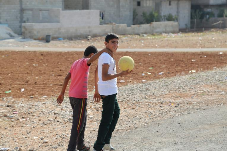 Two Syrian boys play football near an empty field in Sanliurfa, Turkey.