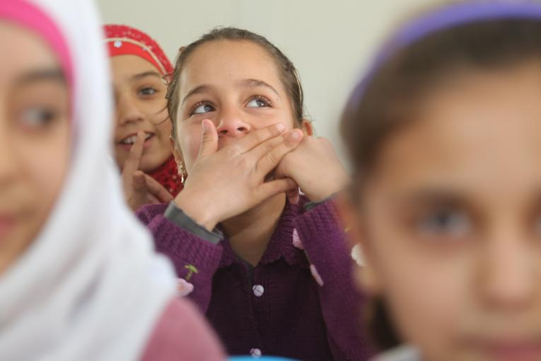 A girl smiles and covers her mouth in a Turkish language class in Nizip 1 refugee camp, Gaziantep, southern Turkey.