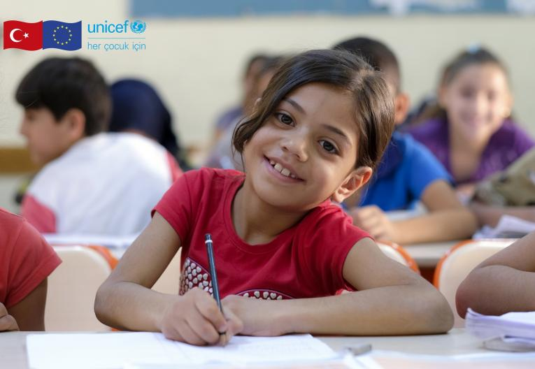 A refugee girl sits writing at a desk in a school in Turkey.
