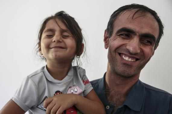 Omid and his daughter enjoy and cuddle and laugh together.