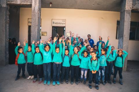 Children of Al Bashayer school line up for a group photo at the school entrance just before their home-time.