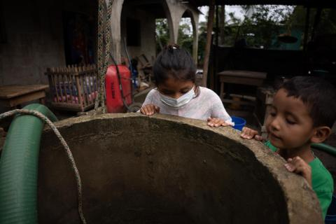 Children observe the cleaning of a well in the Jimeritos community, this community was affected by the storms Eta and Iota, the Motagua River flooded the Jimeritos Community, Izabal, Puerto Barrios, Guatemala.