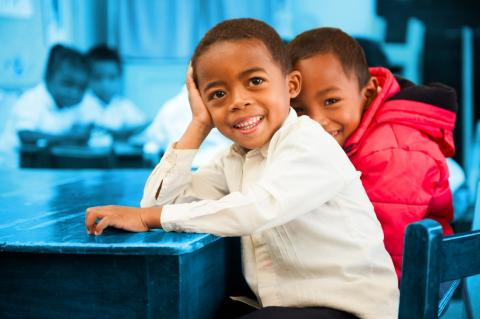 Boys in Madagascar sit smiling at a school desk.