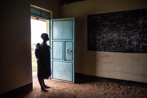 An adolescent girl stands in the doorway of a classroom, her baby held in a wrap on her back.