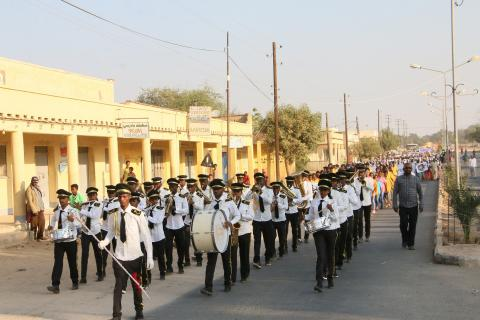 A musical band lead a procession through the streets of Barentu
