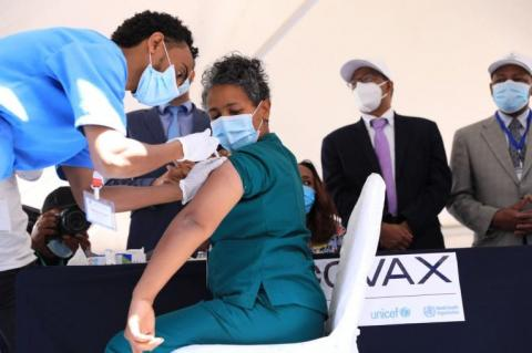 A woman receives a vaccine jab