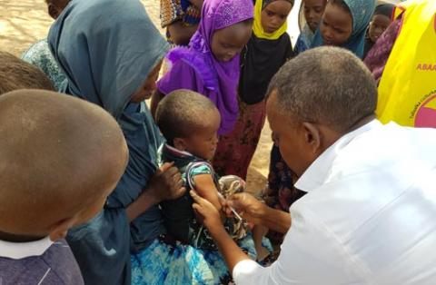A child amongst a crowd is given an injection