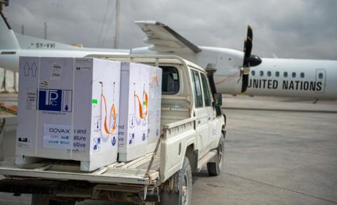 Supplies on a back of truck; an airplane in background