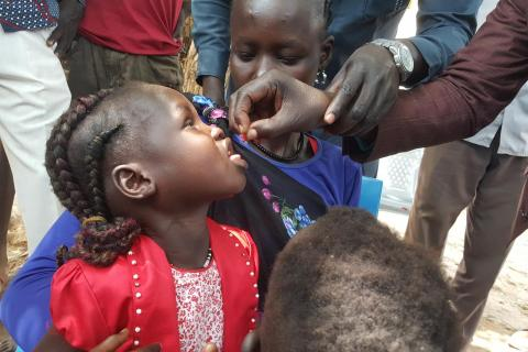 A young child receives a drop into her mouth