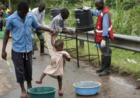 A girl washes her feet and shoes in a sanitation liquid