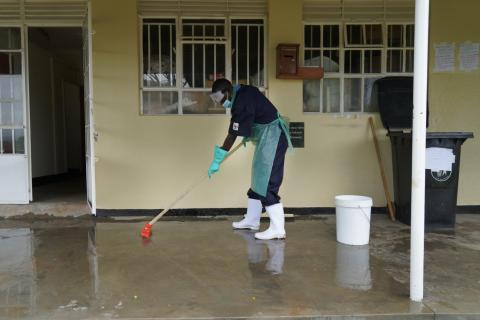 27-year-old Yusto Katahoire, chief hygienist, cleans the floor at a health facility.