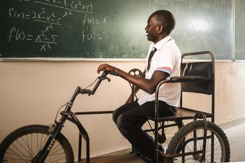 Raul, 20, solves mathematical problems on a blackboard during a class at school in Maputo, Mozambique