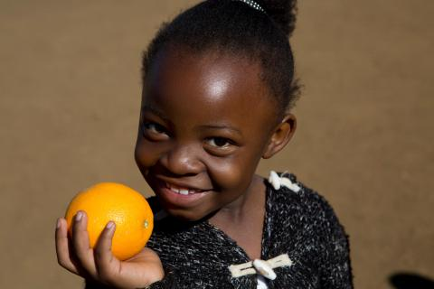 In South Africa, a girl plays with an orange in the Isibindi Safe Park in Soweto.