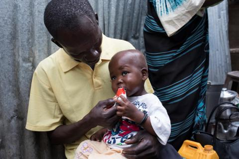 Gift is being fed Plumpy'Nut by his father Yosa Augustino after being treated for malnutrition in Juba, South Sudan.