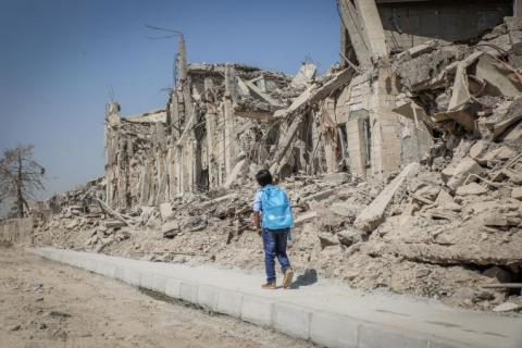 A child walks past buildings that have been destroyed in West Mosul, Iraq.