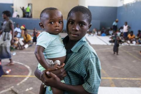 On 21 March 2019 in Mozambique, Helcio Filipe Antonio holds a boy named Anderson Tackdi the Samora Michel High School in Beira. The Samora Michelle High School is one of the places used as a living space for people from Buzi, Mozambique that has been displaced by the floods caused by Cyclone Idai.