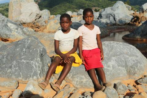 Two children pose against some rocks