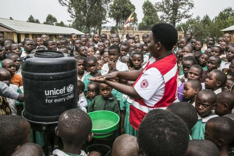 A Uganda Red Cross volunteer demonstrates hand washing methods to pupils of Runyinya Primary school