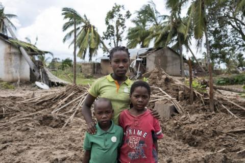 A family stands by a destroyed house.