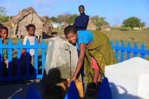 A woman smiles as she collects water from an outdoor tap