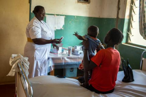 Midwife Akello Filder gives ARV drugs to a young mother holding a 1-year-old child.