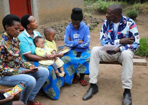 Daniel sits with a family outside their home as he discusses symptoms and prevention measures of Ebola.