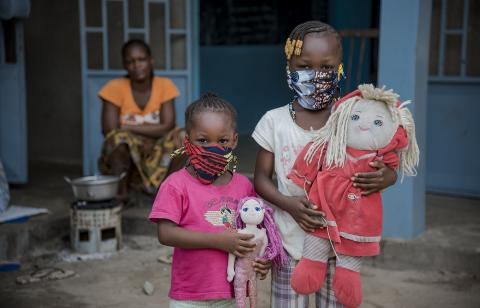 Two young girls holding toys and wearing protective face masks; their mother in the background