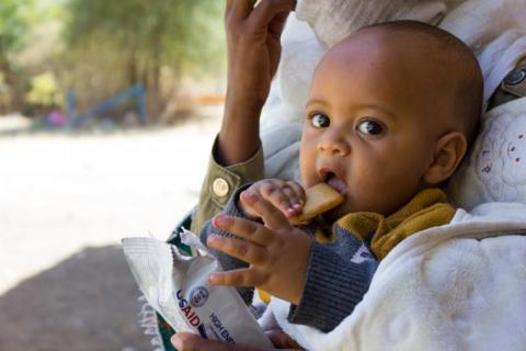 An infant holds food to his mouth