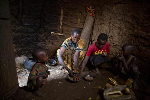Esther, centre, a mother of four children, prepares maize to feed her children in Kibande in Northern Burundi.