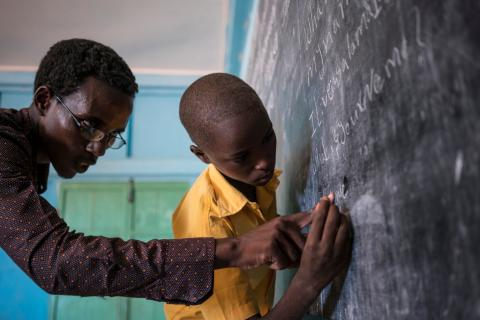 A 10-year old boy receives help from his teacher as he writes the answers to questions up on his classroom chalkboard in his UNICEF-supported primary school in Somalia.