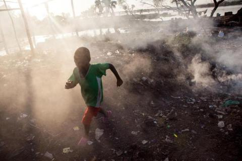 A boy runs through the smoke of burning garbage