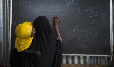 Ismahan, 13, holding her sleeping 3-year-old sister, works on an arithmetic problem at the blackboard, Somalia.