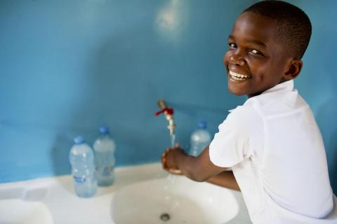 Hans Hasan, a participant of the SWASH club; poses for a photograph while washing her hands at Kingugi School in Dar es Salaam, Tanzania. The SWASH club teaches children the importance of hand washing before eating and after visiting the toilet and encourages children to educate their families and peers of the imporance of having clean hands.