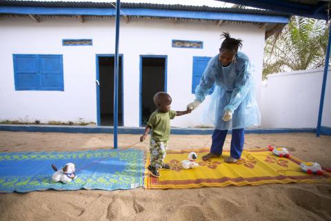 In Guinea, 19 month old Tamba Manzare and caregiver Rose Komano play outdoors at a UNICEF-supported nursery
