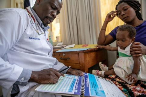 Dr. Denis Nansera, a paediatrician, examines Kansiime Ruth, 25, and her daughters aged 1 and 4 years, at the Mbarara Regional Referral Hospital in Mbarara District, Western Region, Uganda