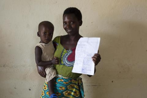 A mother holds her son, 1, alongside his birth certificate.