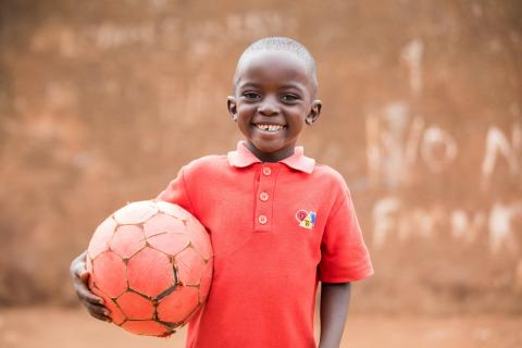 A boy poses holding a ball after a soccer game