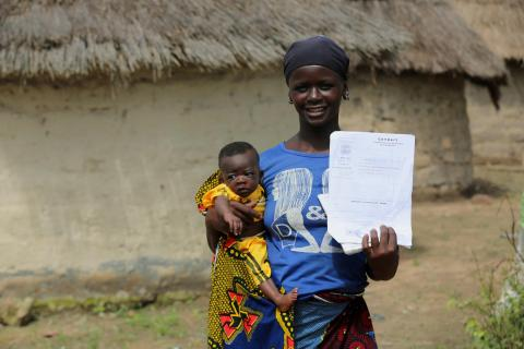 A mother poses  with her baby holding a birth certificate