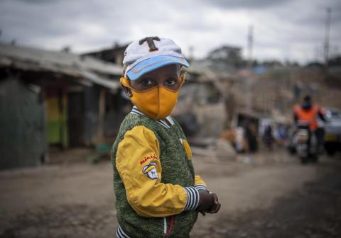 A young boy wears a face mask