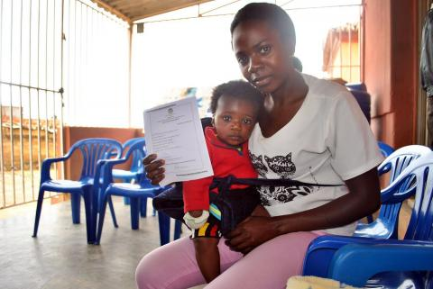 A mother, child on her lap, holds up her son's birth registration certificate.