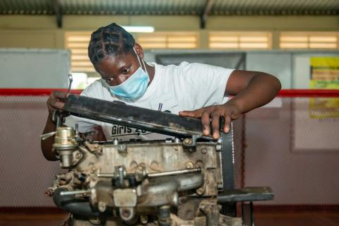 An adolescent girl in protective face mask works on a machine