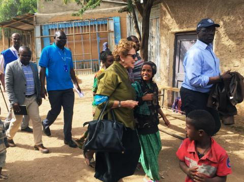 Head of UNICEF walks with children and staff