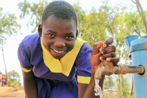 Lucy collects water at her school from a tap that is connected to a solar-powered water pump.
