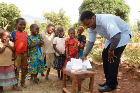 hildren at Mangumba Village in Zomba wait to receive their vitamins from Neverson