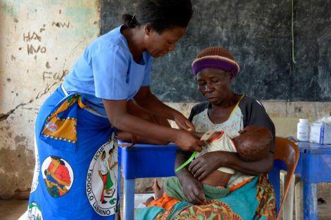 A health worker measures the upper-arm circumference of an infant
