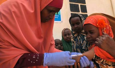 Muna, 6, is vaccinated against measles at the vaccination post in Bay Regional Hospital in Baidoa, Bay Region. She came with three of her sisters, accompanied by their mother.