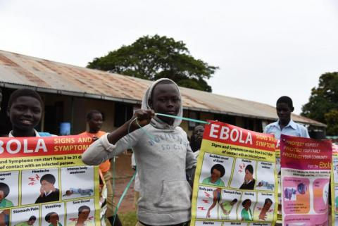A child holds an information poster on Ebola