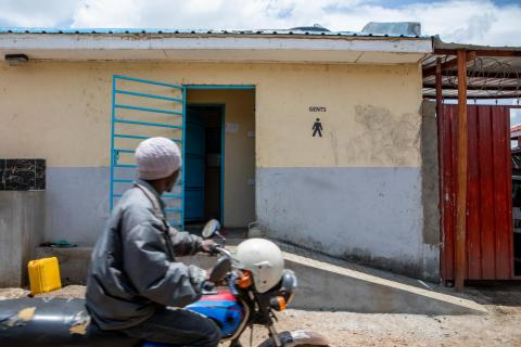 A man on a moped passes a latrine