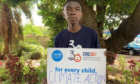 An adolescent boy holds up a climate action sign