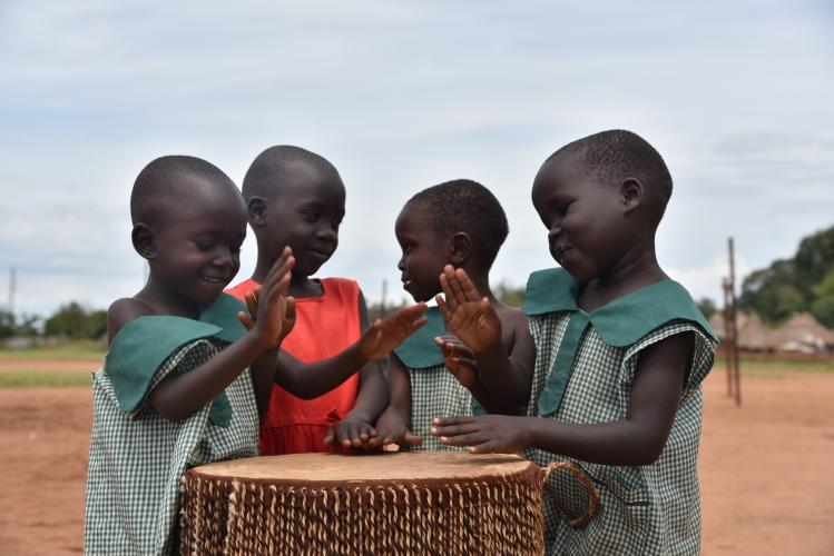oung children have a light moment, while drumming at a UNICEF-supported child friendly space in Adjumani District.